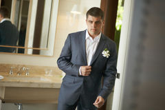 Handsome and strong man putting on official suit. Nice and slender groom wearing wedding suit and putting on cuffs in bedroom looking in mirror Royalty Free Stock Image