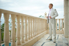 Handsome and strong man putting on official suit. Royalty Free Stock Photography