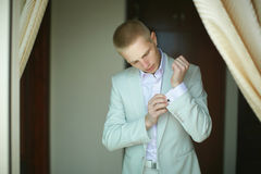 Handsome and strong man putting on official suit. Royalty Free Stock Image