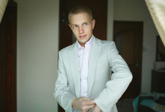 Handsome and strong man putting on official suit. Stock Images