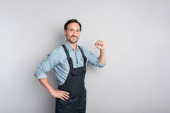 Handsome strong man showing his strength. I can do everything. Good looking charismatic male worker clenching the fist and standing confidently while showing his Royalty Free Stock Photography