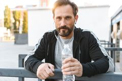 Handsome strong mature sportsman listening music with earphones holding bottle with water. Image of handsome strong mature sportsman sitting outdoors looking Stock Photos