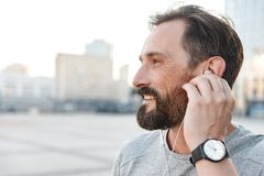 Handsome strong mature sportsman listening music with earphones. Image of handsome strong mature sportsman standing outdoors looking aside listening music with royalty free stock photography