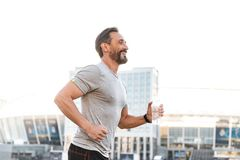 Handsome strong mature sportsman running royalty free stock photography