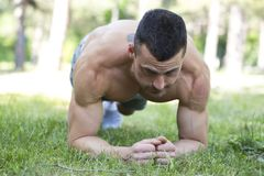 Handsome strong sporty male doing exercises outdoor. Handsome strong sporty male doing push up exercises outdoor. Sport and lifestyle concept Royalty Free Stock Images