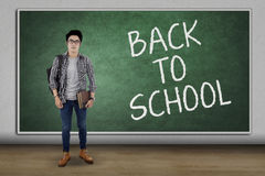 Handsome student back to school. Male high school student standing in the classroom with text of Back To School on the blackboard Stock Images