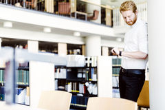 Handsome student checking time in library Stock Image