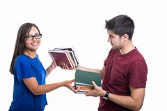 Handsome student couple exchanging bunch of books stock images