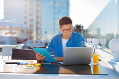 Handsome student doing homework in cafe Royalty Free Stock Photography