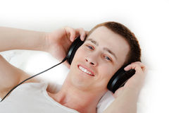 Handsome student enjoying music. Student is laying down on bed enjoying the music and golding his headphones Stock Photos