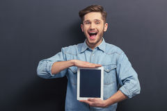 Handsome student with gadget. Handsome young student is showing a laptop, looking at camera and smiling, standing against blackboard Royalty Free Stock Images