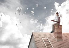 Handsome student guy reading book and aerostats flying in air Stock Photography