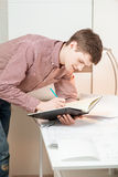 Handsome student leaning against table and writing in textbook Royalty Free Stock Photography