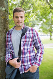 Handsome student leaning on tree looking at camera Stock Images