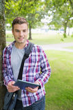 Handsome student leaning on tree looking at camera holding tablet Stock Photography