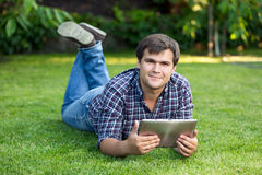 Handsome student lying in park on meadow with digital tablet Stock Images