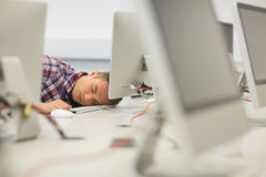 Handsome student napping in the computer room Royalty Free Stock Photos