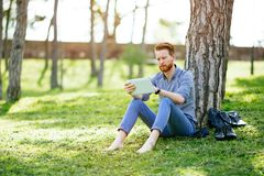 Handsome student reading in nature. Handsome student reading and studying in park Royalty Free Stock Photos