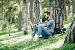 Handsome student reading in nature. Handsome student reading and studying in park Stock Photo