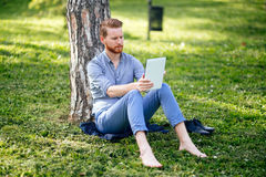 Handsome student reading in nature. Handsome student reading and studying in park Stock Photography