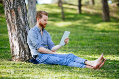 Handsome student reading in nature. Handsome student reading and studying in park Royalty Free Stock Photography