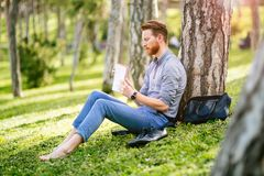 Handsome student reading in nature. Handsome student reading and studying in park Stock Photos