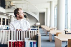 Handsome student searching for a book in a library Stock Images