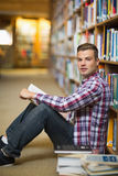 Handsome student sitting on library floor reading. In college Royalty Free Stock Photos