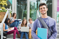 Handsome student smiling at camera outside. At the university Stock Photos
