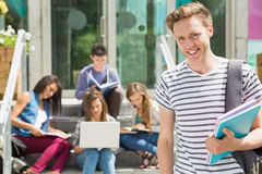 Handsome student smiling at camera outside. At the university Royalty Free Stock Photos