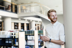 Handsome student smiling in library Royalty Free Stock Images