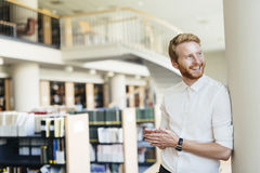 Handsome student smiling in library Royalty Free Stock Photography