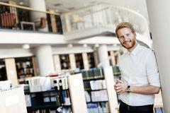Handsome student smiling in library. Handsome intelligent male student smiling in library Royalty Free Stock Image