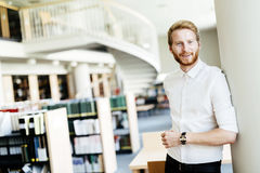 Handsome student smiling in library. Handsome intelligent male student smiling in library Royalty Free Stock Photo
