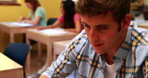 Handsome student smiling to camera in classroom stock video footage