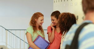 Handsome student walking past group of giggling girls Stock Photos