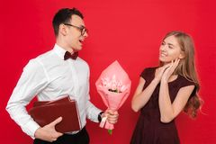 A handsome student, wearing glasses, gives a gift and a bouquet of flowers to his girlfriend against a red background royalty free stock photos