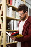 Handsome student wearing glasses reading book in library Stock Image