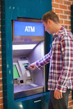 Handsome student withdrawing cash royalty free stock photography