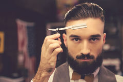 Handsome stylish barber. Handsome bearded hairdresser in stylish classic wear is holding a straight razor while standing at the barbershop Royalty Free Stock Images