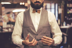 Handsome stylish barber. Cropped image of bearded barber in stylish classic wear holding a straight razor Stock Photos