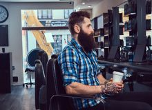 Handsome bearded man in the barbershop. A handsome stylish bearded male with a tattoo on arm dressed in a flannel shirt drinks coffee in a barbershop royalty free stock images