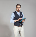 Handsome stylish bearded man in classic vest holding tablet Royalty Free Stock Images