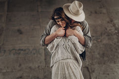 Handsome stylish cowboy man in hat and shirt embracing beautiful. Handsome stylish cowboy men in hat and shirt embracing beautiful gypsu women from behind Stock Photos