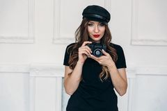 Handsome stylish girl photographer, wearing a black T-shirt without prints, and a cap, coloring her lips with red royalty free stock photos