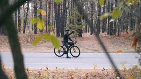 Handsome stylish guy in black clothes, helmet and sports sunglasses with road bike standing in fall city park and taking selfie or. Photos on phone. Autumn stock footage