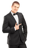 Handsome stylish male in bow tie suit pointing. Isolated on white background Stock Photography