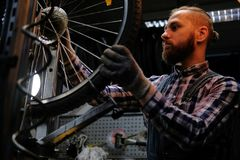 Handsome stylish male wearing a flannel shirt and jeans coverall, working with a bicycle wheel in a repair shop. A handsome stylish male wearing a flannel shirt Royalty Free Stock Photography