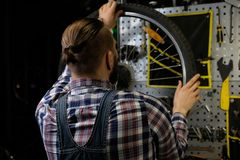 Handsome stylish male wearing a flannel shirt and jeans coverall, working with a bicycle wheel in a repair shop. A handsome stylish male wearing a flannel shirt Stock Photography