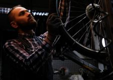 Handsome stylish male wearing a flannel shirt and jeans coverall, working with a bicycle wheel in a repair shop. A handsome stylish male wearing a flannel shirt Stock Photos